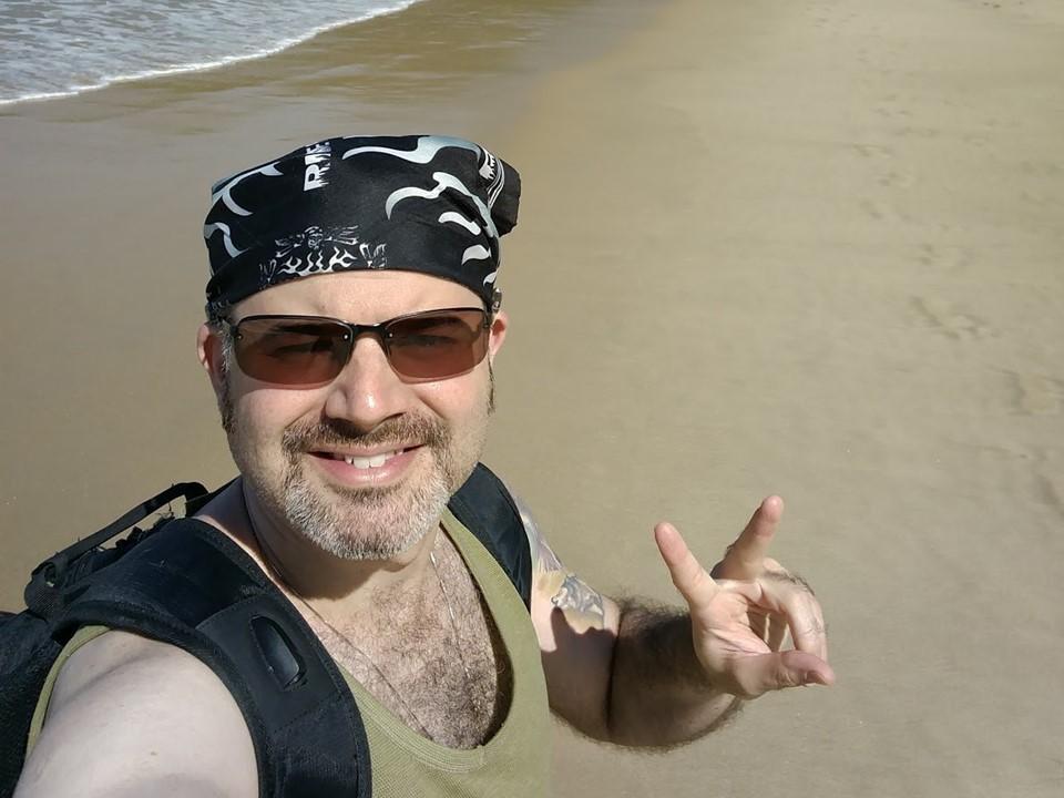 Nelson Azambuja Jr. está em pé, sorrindo, fazendo o gesto de V com uma das mãos em uma praia em um dia ensolarado. Ele tem barba, está usando óculos escuros, bandana preta na cabeça, mochila nas costas e uma blusa regata.