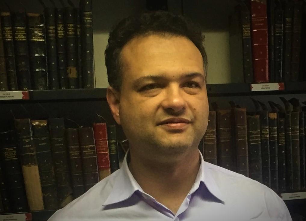 Carlos Ferrari com leve sorriso no rosto. Ele tem cabelos curtos castanhos escuros. Ao fundo, há uma estante com livros.