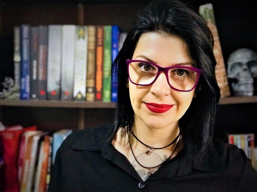 Débora Brandão está com um leve sorriso. Ela tem cabelos negros e lisos, está usando óculos e batom vermelho. Ao fundo, há uma estante com diversos livros.