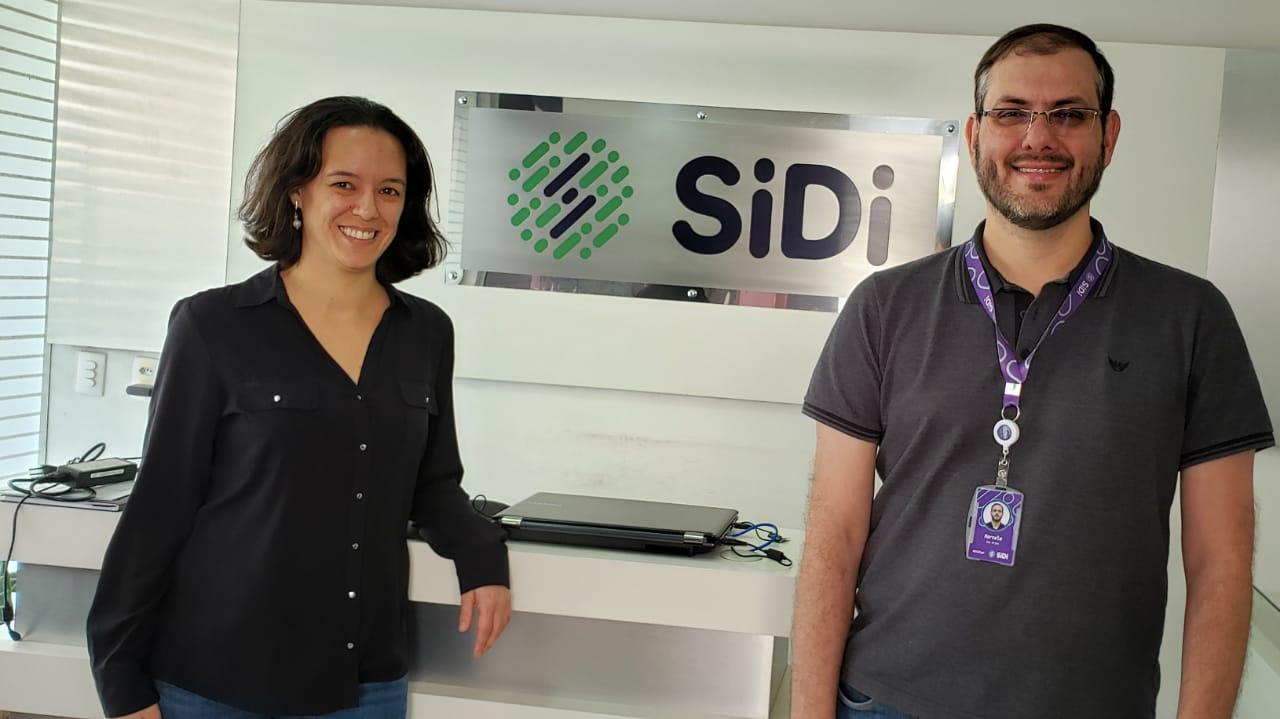 """Fernanda Kussama Pellegrini e Marcelo Anjos estão em pé, sorrindo, em um ambiente fechado. Ao fundo, há uma placa com o nome """"SiDi""""."""
