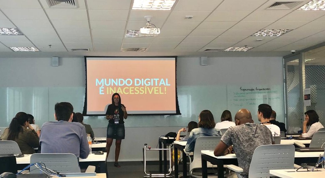 """Simone Freire está em pé, falando, olhando para pessoas que estão sentadas em carteiras de estudante em uma sala de aula. Ao fundo, há um telão com o texto: """"Mundo digital é inacessível""""."""