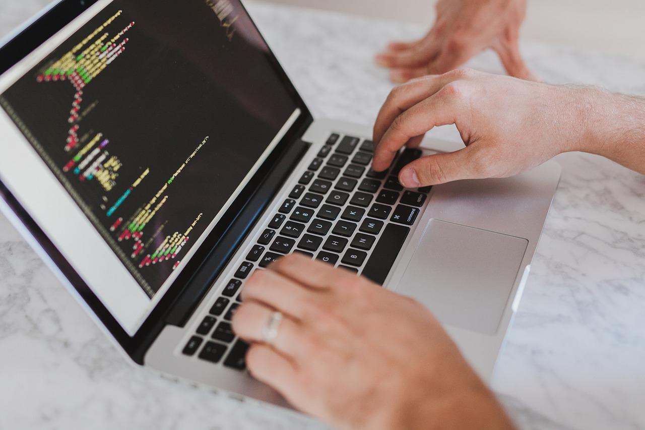 Duas mãos de uma pessoa estão em cima do teclado de um laptop que mostra a tela preta com diversos códigos.