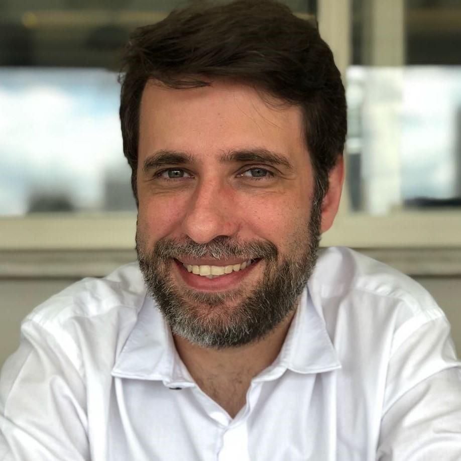 Reinaldo Ferraz está sorrindo. Ele tem cabelos curtos, barba e olhos claros.