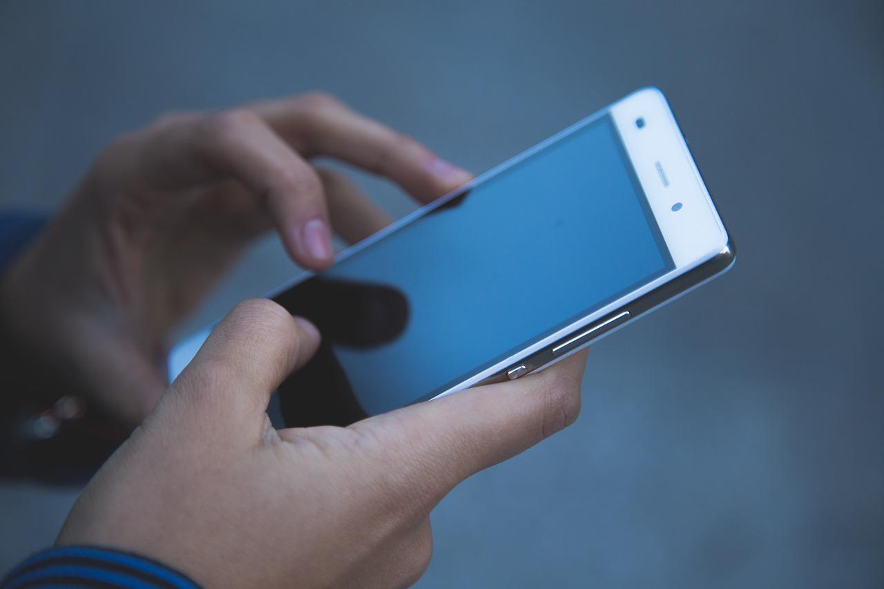 Pessoa segura smarthphone com as duas mãos. Um dos dedos toca a tela.