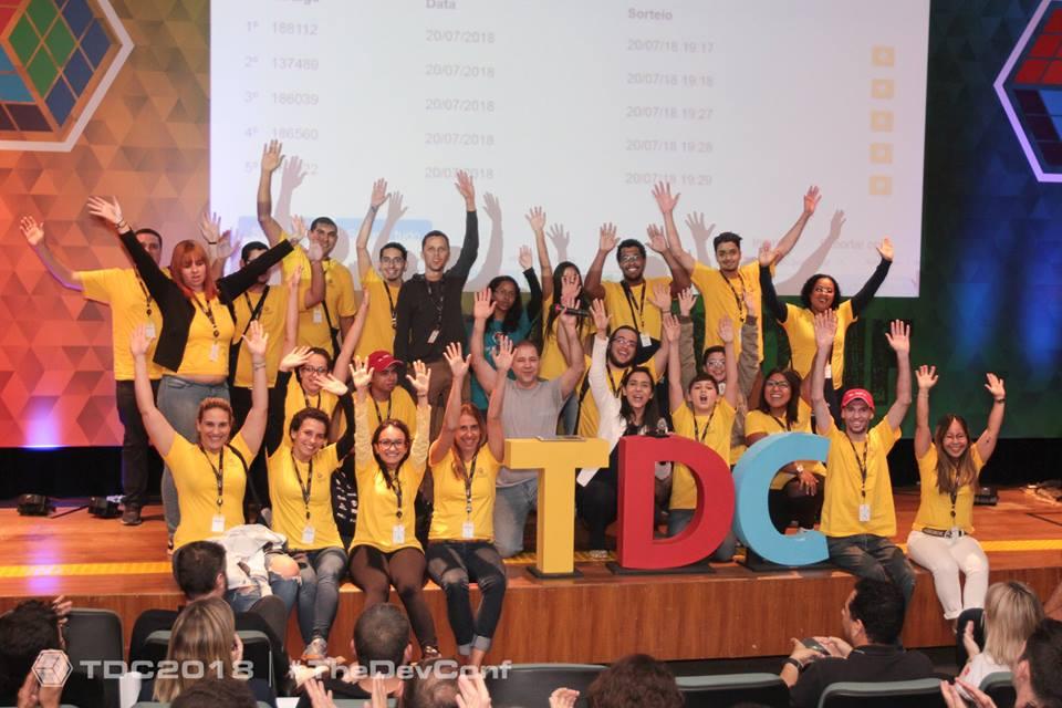 Grupo de pessoas em pé e sentadas em cima de um palco ao redor das letras TDC. A maioria está vestida com uma blusa amarela e está sorrindo com as mãos para cima.