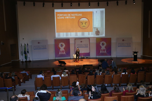 Simone Freire está em pé, falando ao microfone em um palco na frente de diversas pessoas que estão sentadas.
