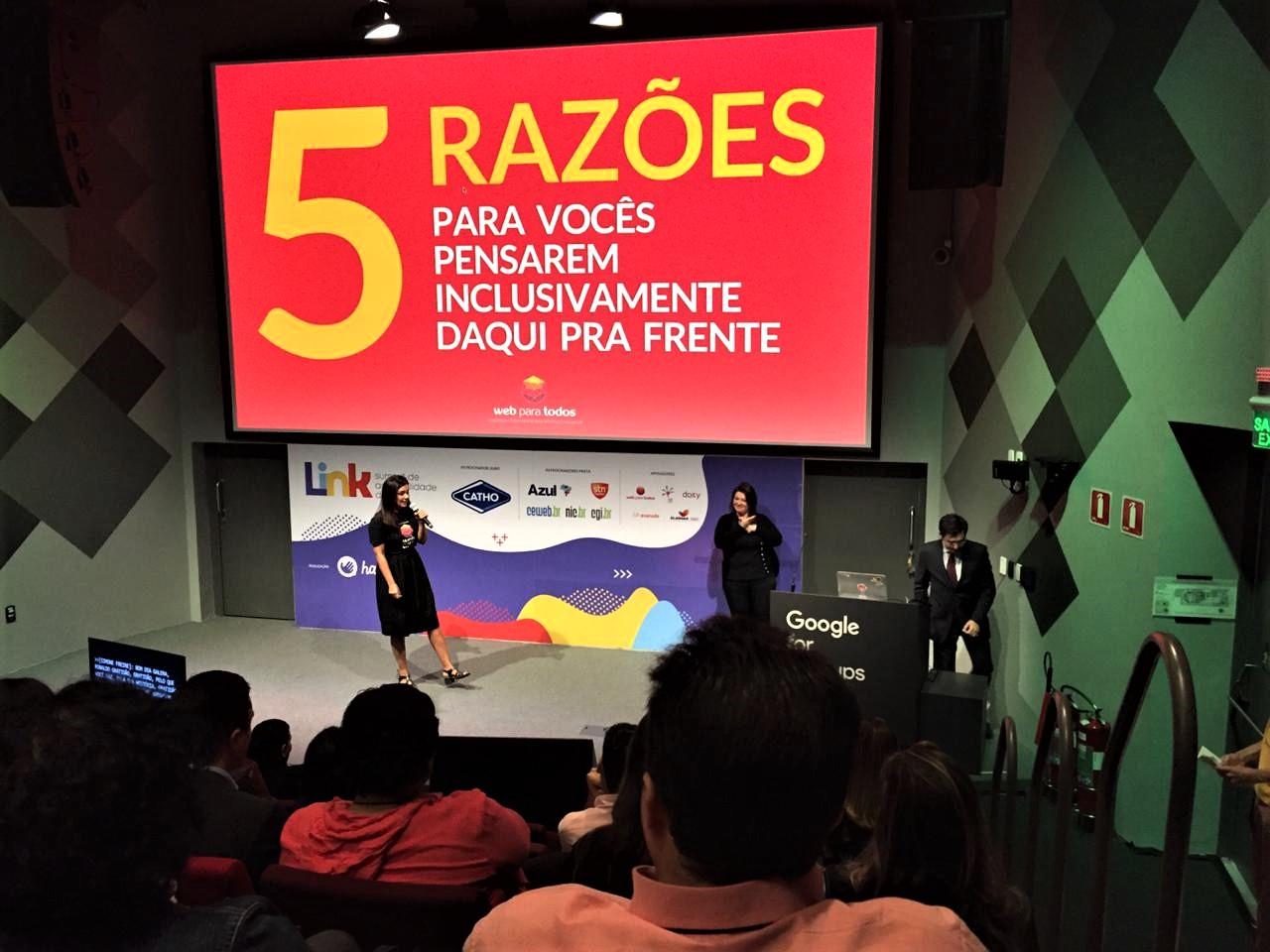 Simone Freire está em pé, segurando um microfone no palco do auditório do Google Campus São Paulo.