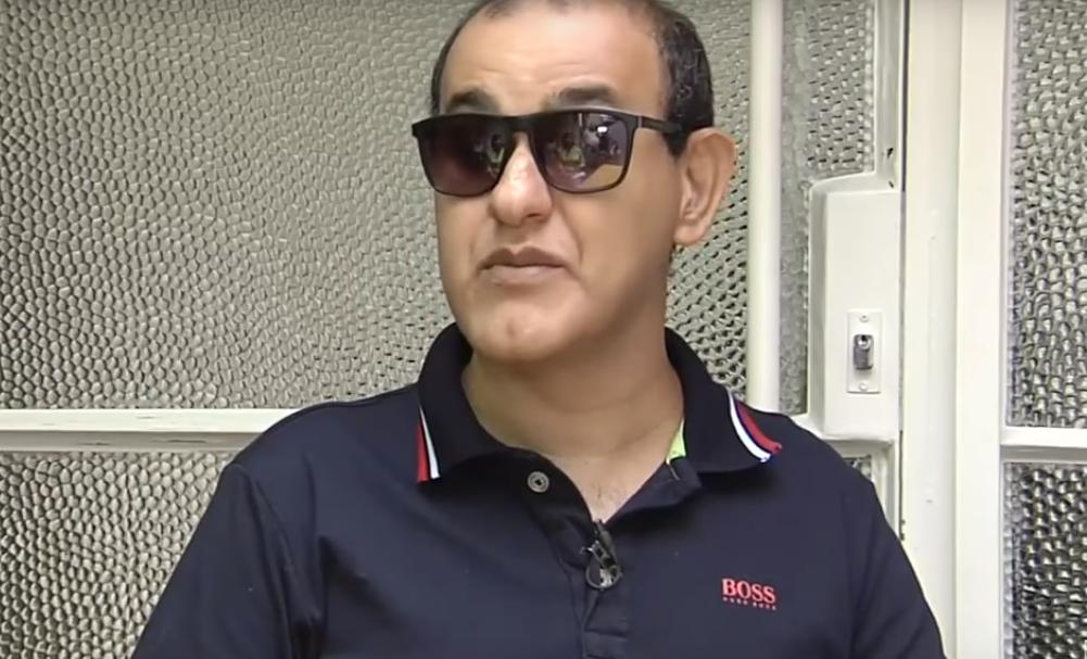 Beto Pereira é moreno, calvo, usa óculos escuros e camisa azul.