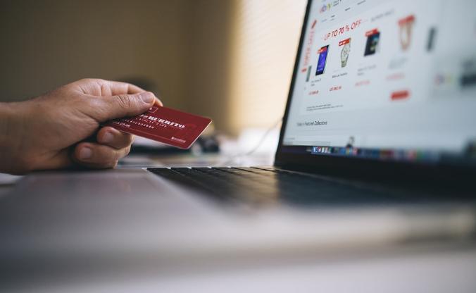 Pessoa segura cartão de crédito ao lado de um llaptop mostrando produtos na tela.