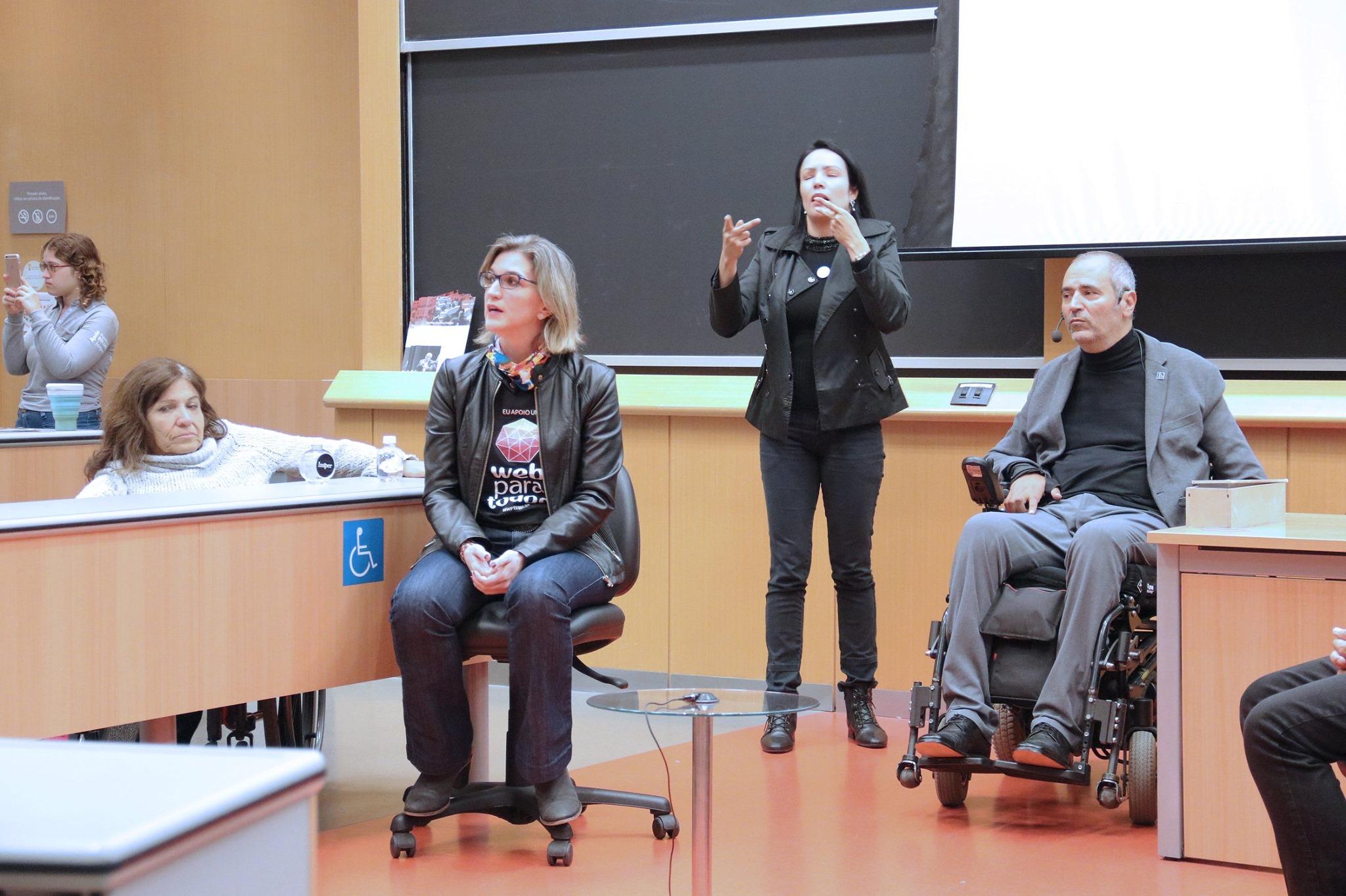 Foto da SuzelI Damaceno sentada ao lado do Cid Torquato e de uma intérprete de libras, que está em pé. Ao fundo, há um quadro negro.