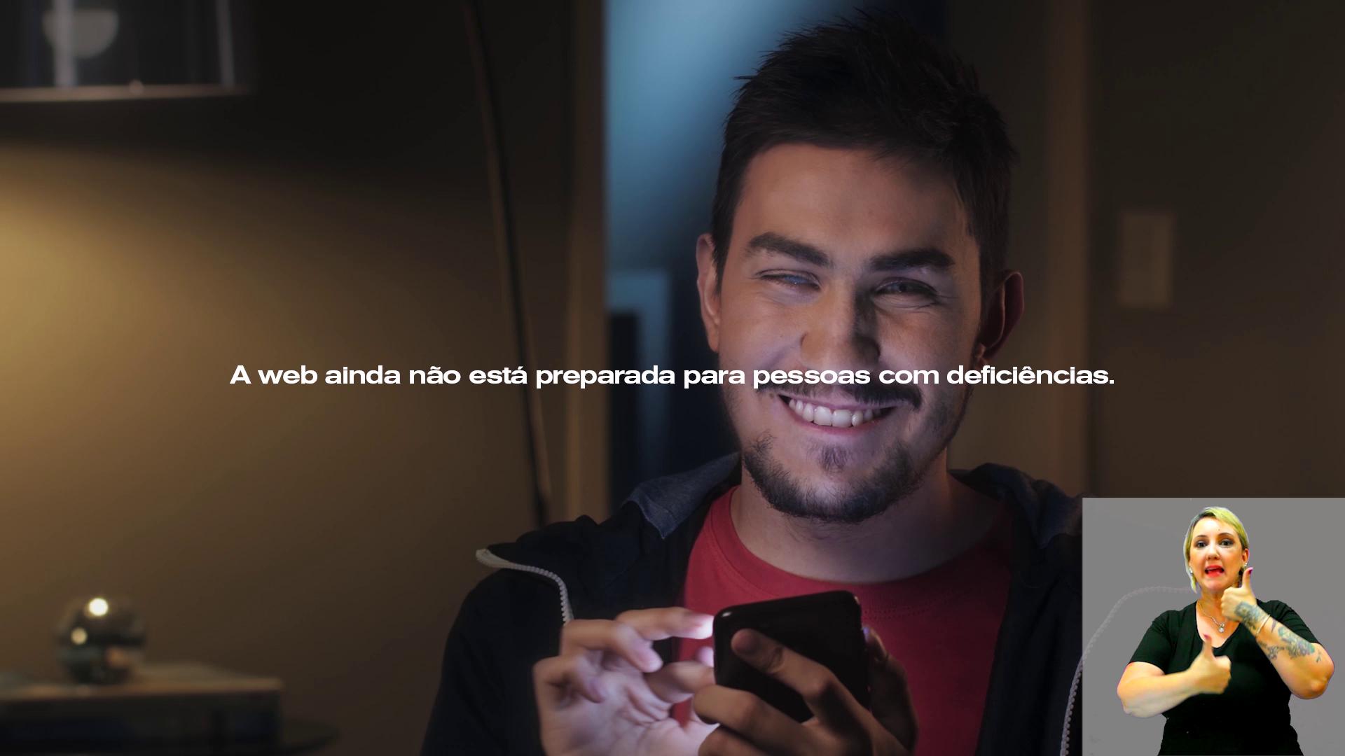 Foto de um rapaz segurando um celular e sorrindo. Há uma frase com fonte branca também.
