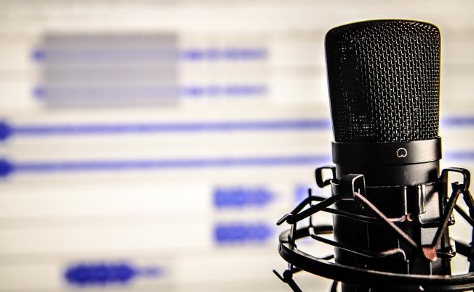 Foto de um microfone na frente da tela de um computador.