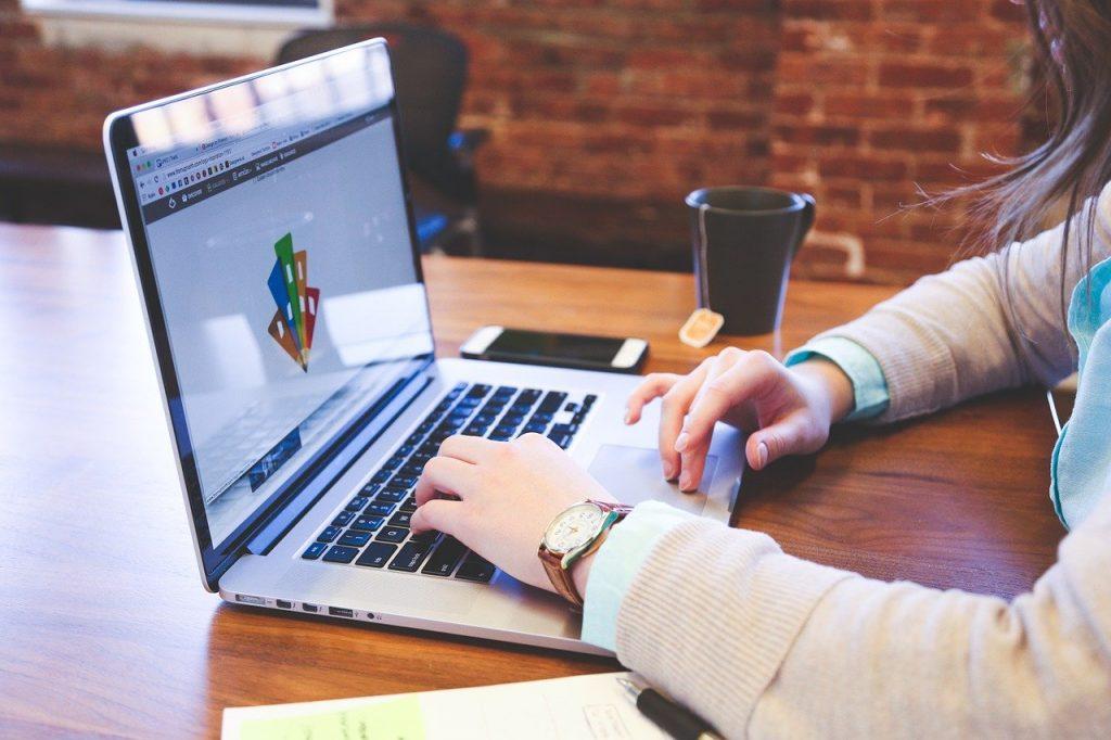 Foto de uma pessoa digitando em um laptop. Há uma caneca com chá ao lado e um smartphone.