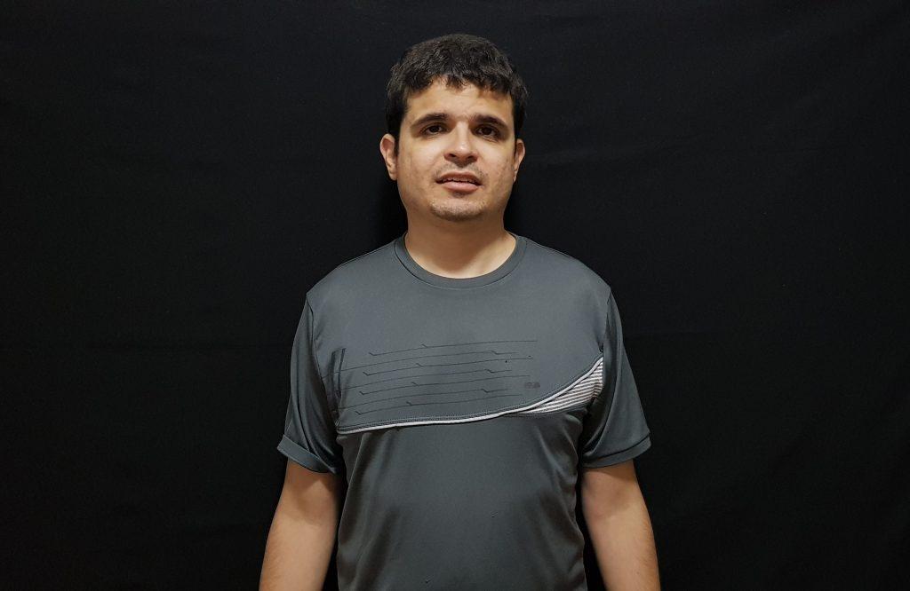 Foto do Diniz Candido em pé com leve sorriso. Ele tem cabelos curtos, castanhos e está usando uma blusa na cor cinza.
