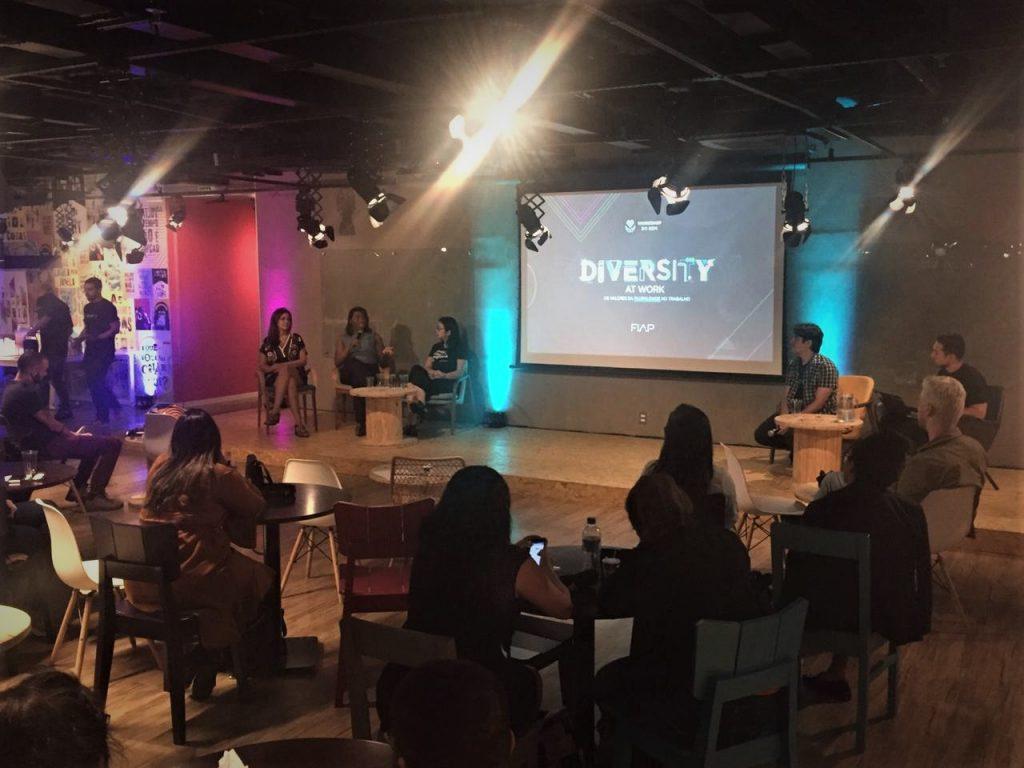 """Foto da Yasmin Vitoria, sentada, falando ao microfone em uma sala com diversas pessoas sentadas. Ao fundo, há um telão com o texto: """"Diversity""""."""