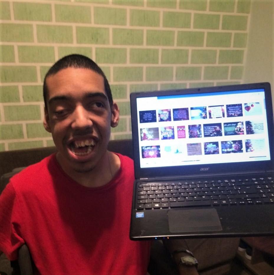 Foto do Gabriel Sangioratto sorrindo. Ele tem cabelos curtos e usa uma blusa vermelha. Há um laptop ao lado dele, ligado, que mostra diversas imagens.