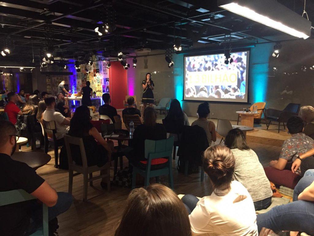 Foto da Simone Freire, em pé, falando ao microfone em uma sala. Ela está na frente de diversas pessoas que estão sentadas ao redor de mesas redondas. Ao fundo, há um telão com o texto: '1,3 bilhão'.