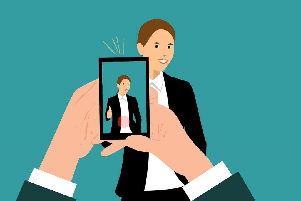 Ilustração das mãos de uma pessoa segurando um smartphone na direção de uma outra que está em pé, olhando na direção do equipamento. A tela dele mostra a imagem da pessoa que sorri e faz o sinal de positivo com uma das mãos. Ainda na tela, há um círculo vermelho no rodapé.