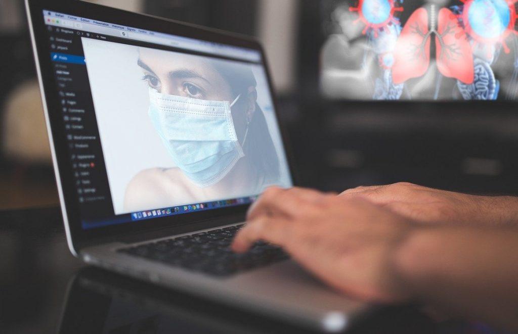Foto de duas mãos em um teclado de um laptop. A tela mostra uma pessoa com máscara e, ao fundo, há uma ilustração de um pulmão com símbolos do vírus coronavírus.