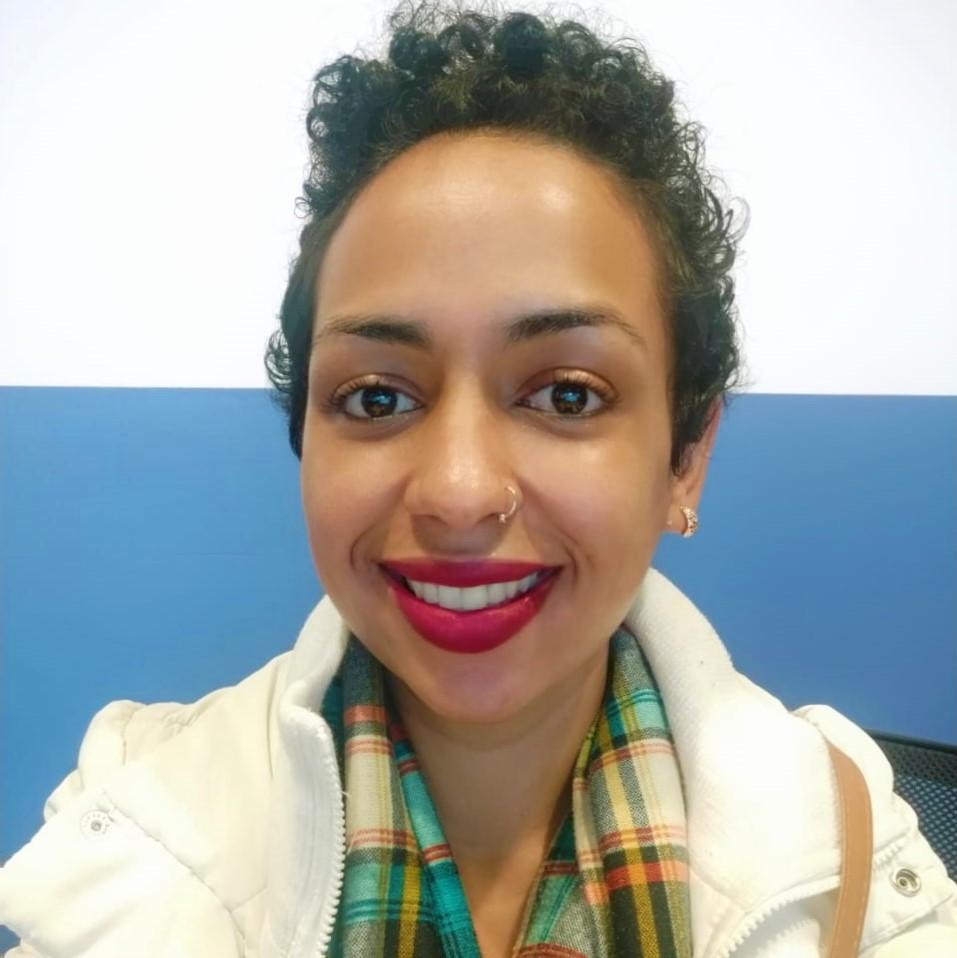 Foto da Nayara sorrindo. Ela tem cabelos encaracolados castanhos e curtos. Usa um brinco pequeno, um piercing no nariz e batom vermelho.
