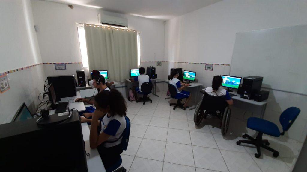 Foto de crianças e jovens sentados na frente de seus respectivos computadores em uma sala. Há uma criança em uma cadeira de rodas. As telas mostram desenhos.