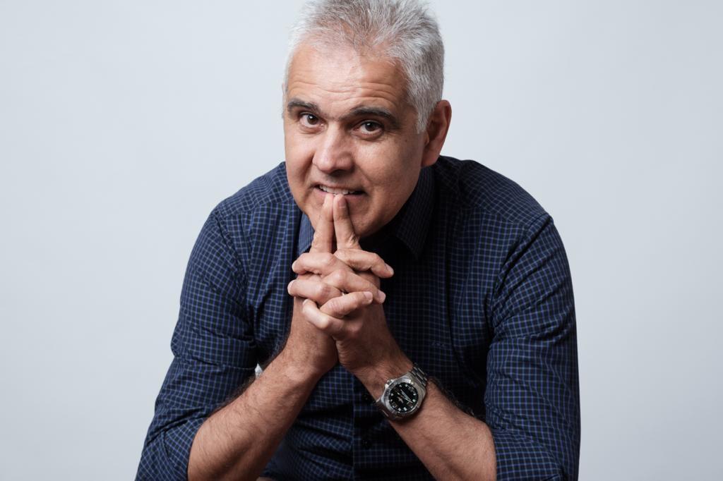 Foto do João Bezerra sorrindo, com as duas mãos juntas e os dedos indicadores próximos à boca. Ele tem cabelos curtos e grisalhos e usa uma blusa quadriculada com mangas compridas.