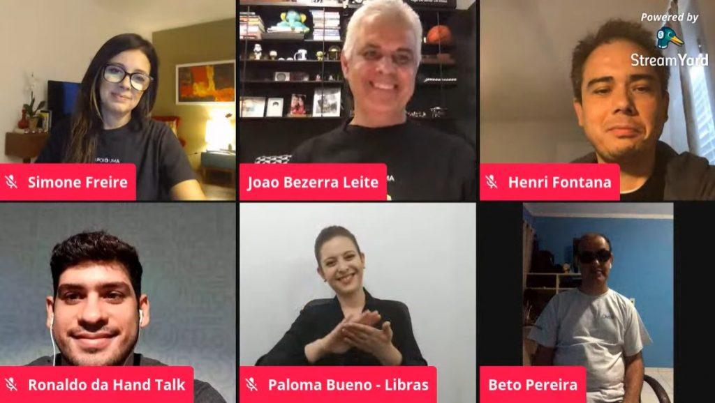 Captura de tela da transmissão da live exibe os rostos dos seis convidados, separados em pequenos retângulos dispostos lado a lado. Da esquerda para a direita: Simone Freire, João Bezerra Leite, Henri Fontana, Ronaldo Tenório, Paloma Bueno (intérprete de Libras) e Beto Pereira.