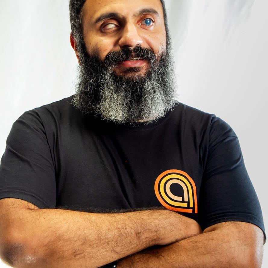 Foto do Alexandre Santos Costa com os braços cruzados e sorrindo. Ele tem cabelos curtos, barba longa. O olho direito tem uma cor branco-azulada e o esquerdo é branco.