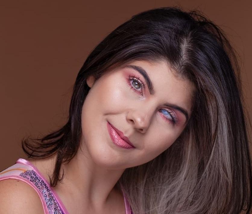 Foto da Isa Meirelles com um leve sorriso. Ela tem cabelos lisos e longos, castanhos claros, na altura dos ombros, tem os olhos claros. Um deles é azul esbranquiçado. Isa usa uma blusa rosa com lantejoulas brilhantes.