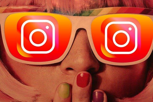 Ilustração de uma pessoa loira com óculos, que estão com logo do Instagram em cada lente na cor laranja em degradê. Ela está com as mãos abaixo do nariz, com unhas pintadas com cores diversas.