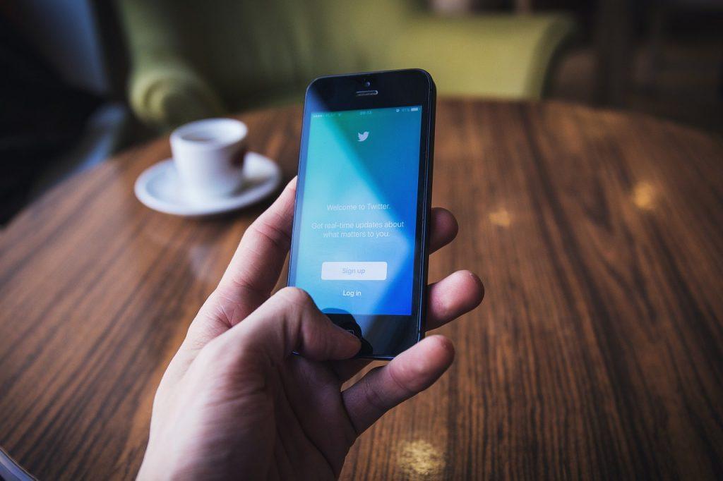 Foto da mão de uma pessoa segurando um smartphone ligado com a tela inicial do Twitter. Ao fundo, há uma mesa de madeira e uma xícara branca.