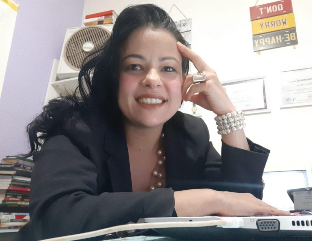 Foto da Morgana Siqueira em um ambiente fechado. Ela sorri e está com uma das mãos apoiadas na cabeça. Morgana tem cabelos longos, ondulados e pretos, usa colar e pulseira de pérolas e um anel grande em uma das mãos. A outra mão está em cima de um laptop.