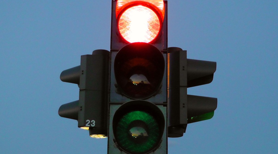 Foto de um semáforo de trânsito com a luz vermelha acesa. Ao fundo, há um céu azul.