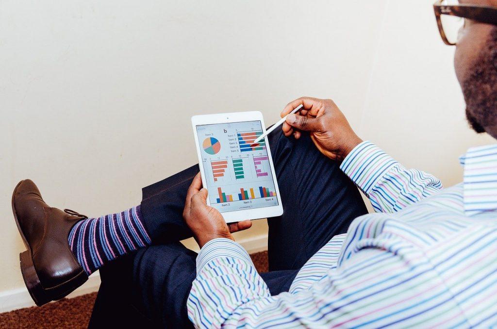 Foto de um homem sentado com as pernas cruzadas. Ele segura um tablet que mostra diversos gráficos coloridos na tela. Uma das mãos segura o aparelho enquanto a outra segura uma caneta touch. Ele usa uma roupa social e meias coloridas.