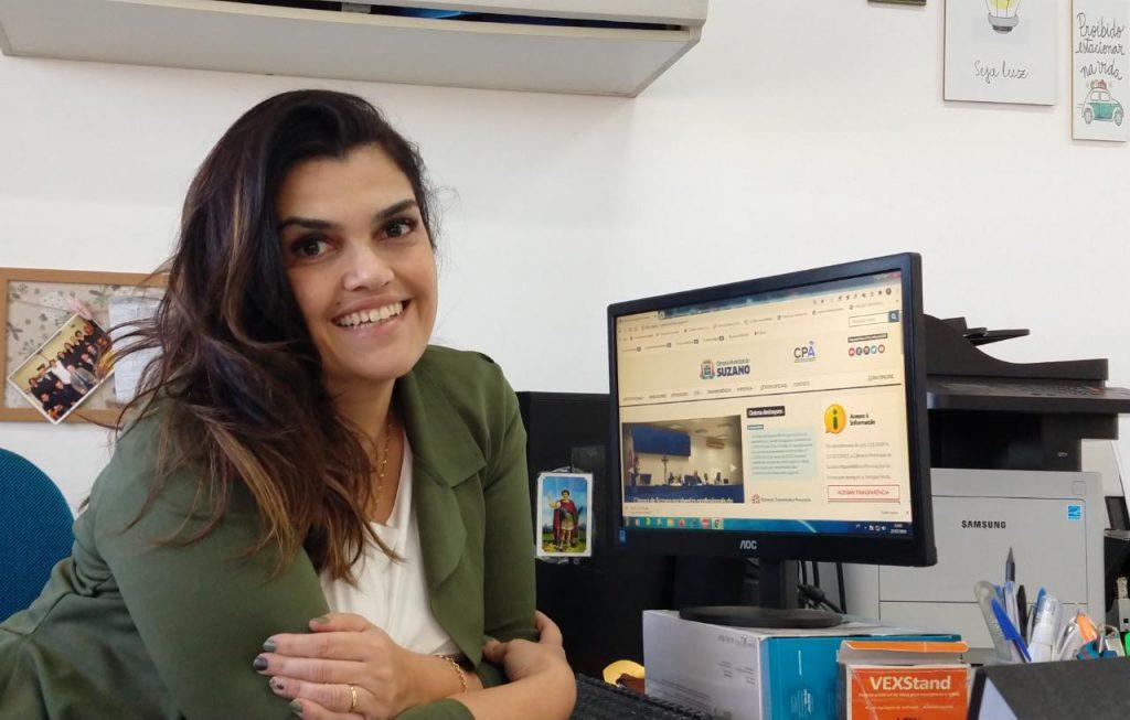Foto da Taiane Fernandes em um ambiente fechado, ao lado de um computador. Ela sorri e está  sentada com os braços cruzados. A tela do computador mostra a página inicial da Câmara Municipal de Suzano.