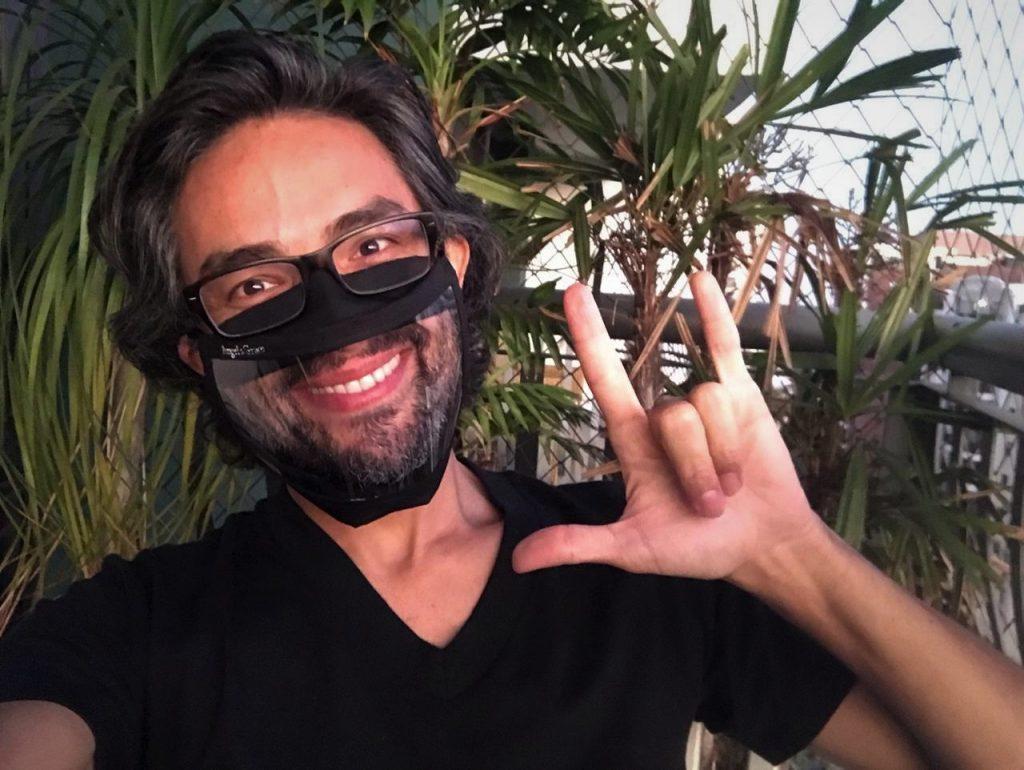 """Foto do Alexandre Ohkawa em uma área externa, durante o dia. Ele sorri e faz o sinal """"I love you"""". Ele tem cabelos curtos e lisos, barba grisalha. Usa óculos preto, blusa preta e uma máscara preta com parte transparente na área da boca, que mostra seu sorriso. Ao fundo, há algumas plantas."""