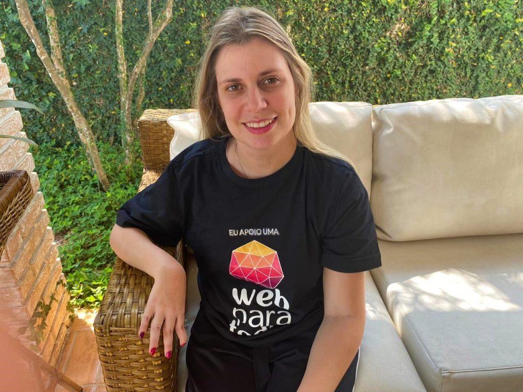 Foto da Nathalia Blagevitch sentada em um sofá, que está em uma área externa, durante o dia. Ela sorri. Nathalia é loira, tem cabelos longos e lisos e usa uma blusa preta com o logotipo do Movimento Web para Todos.