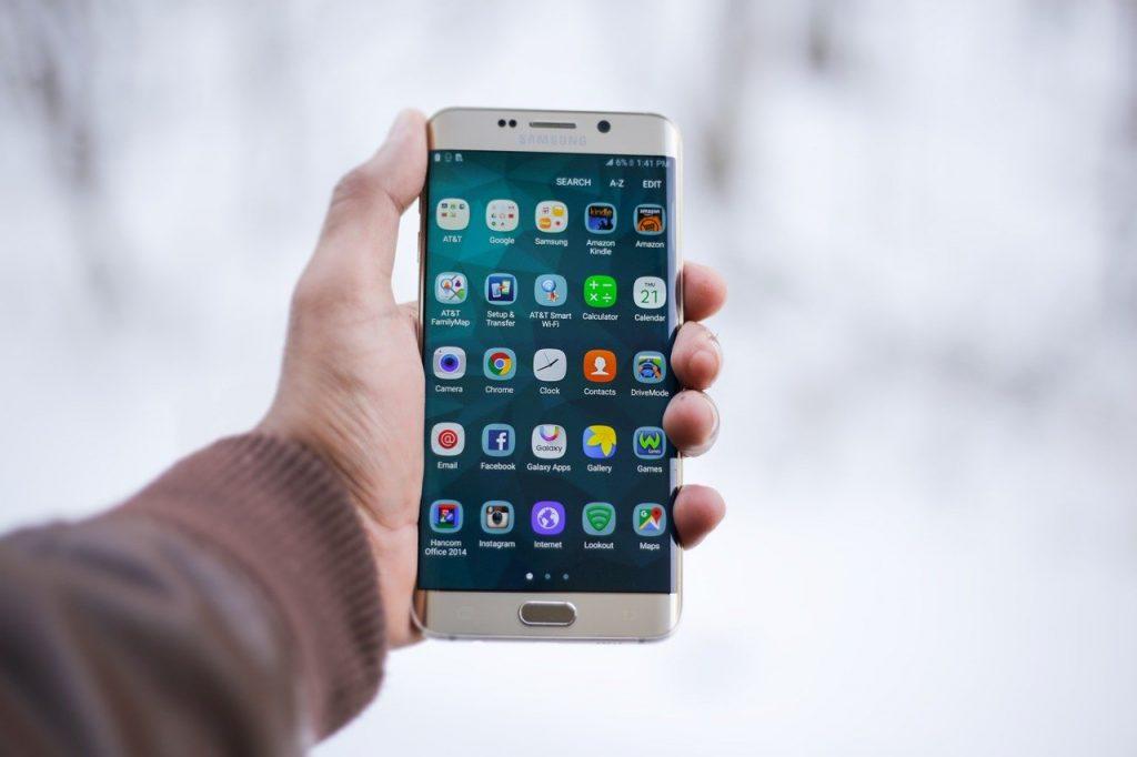 Foto da mão de uma pessoa que segura um smartphone. A tela do equipamento exibe diversos aplicativos.