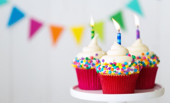 Foto em close de três cupcakes coloridos com velas acesas. Na parede ao fundo, há bandeirinhas de cores variadas desfocadas.