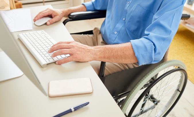 Foto de uma pessoa sentada em uma cadeira de rodas em frente a um computador. Ela está com uma das mãos no teclado e a outra no mouse.
