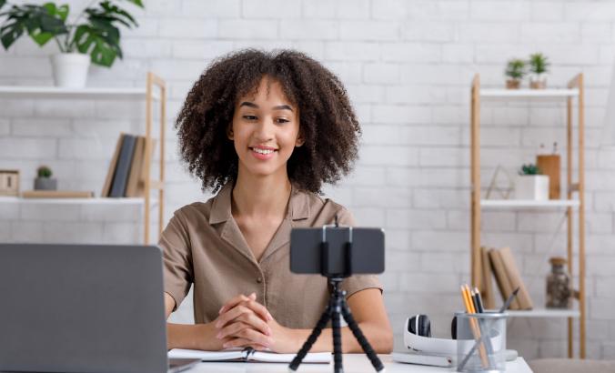 Foto de uma mulher negra sentada na frente de um laptop e de um smartphone que está em um tripé. Ela sorri.