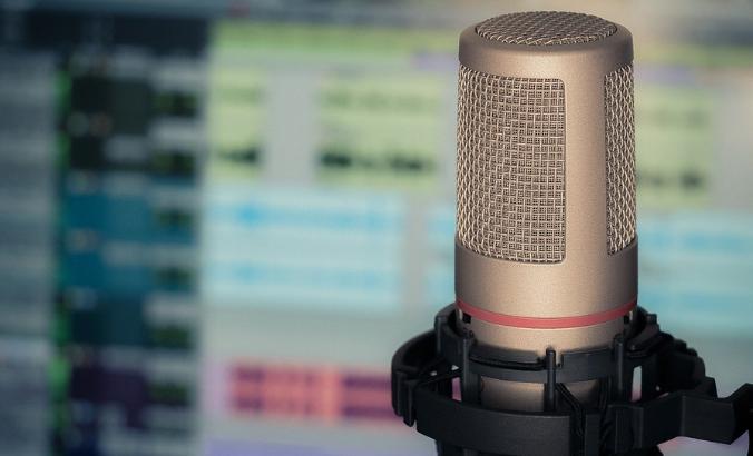 Foto com um microfone e a tela de um computador ao fundo.