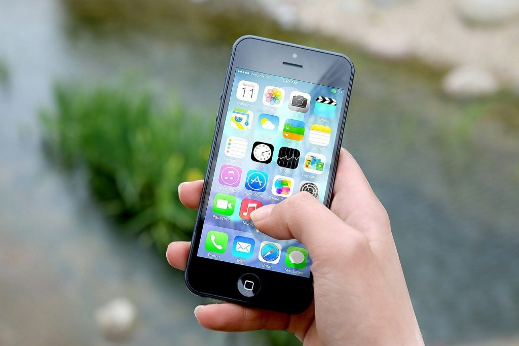 Foto da mão de uma pessoa que segura um smartphone com diversos aplicativos na tela, em que está o dedo polegar.