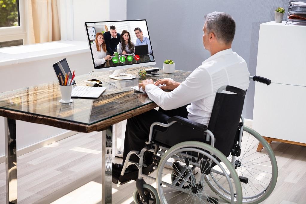 Foto de um homem grisalho, sentado em uma cadeira de rodas, com traje executivo. Acomodado em uma mesa de trabalho, ele tem as mãos sobre o teclado e olha para o monitor à sua frente, que exibe quatro pessoas em uma reunião virtual.