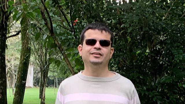 Foto de Diniz Candido em uma área externa arborizada. Ele possui cabelos bem curtos castanhos escuros, usa cavanhaque, está de óculos escuros e apresenta um leve sorriso no rosto.