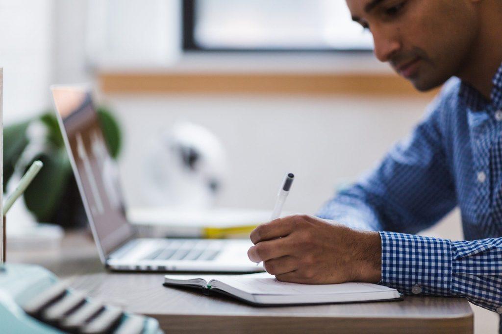 Foto de um homem sentado em uma mesa com laptop e caderno à sua frente. Ele segura uma caneta e olha para o caderno.