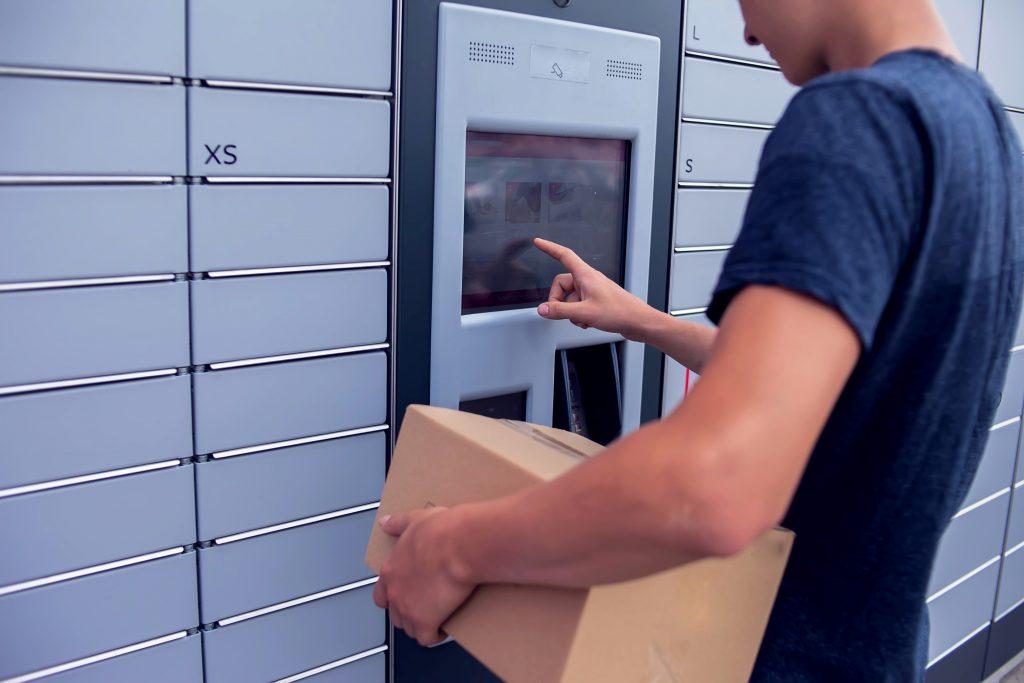 Foto de um rapaz em frente a um terminal de autoatendimento. Ele está de perfil e toca tela do terminal com seu polegar direito. Com a mão esquerda ele segura uma caixa de papelão.