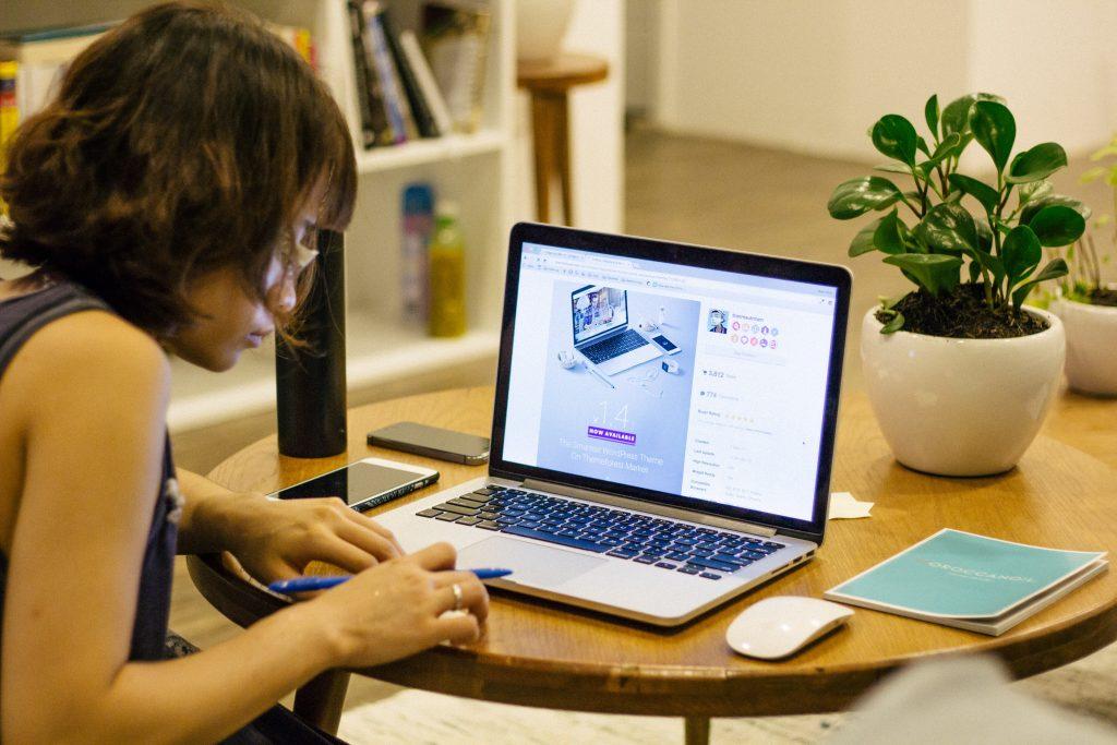 Foto de mulher de perfil sentada em frente a uma mesa com computador, celulares, vasos e um caderno. Ela segura uma caneta e olha para baixo. Na tela de seu computador está projetado um tema do WordPress.