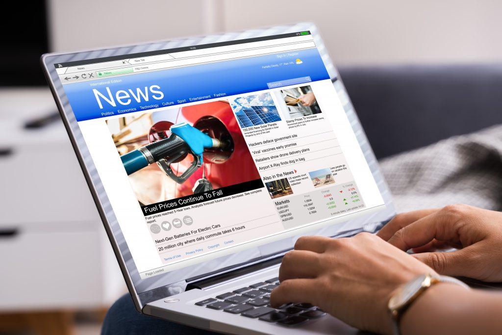 Foto de um notebook apoiado sobre as pernas de uma pessoa. Ela está com as mãos no teclado e na tela está projetada a homepage de um site de notícias.