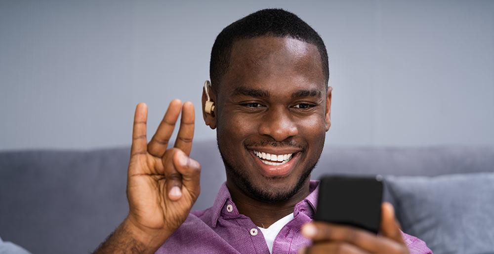 Foto de um homem negro com um aparelho auditivo, ele sorri olhando para o celular enquanto faz um sinal em Libras